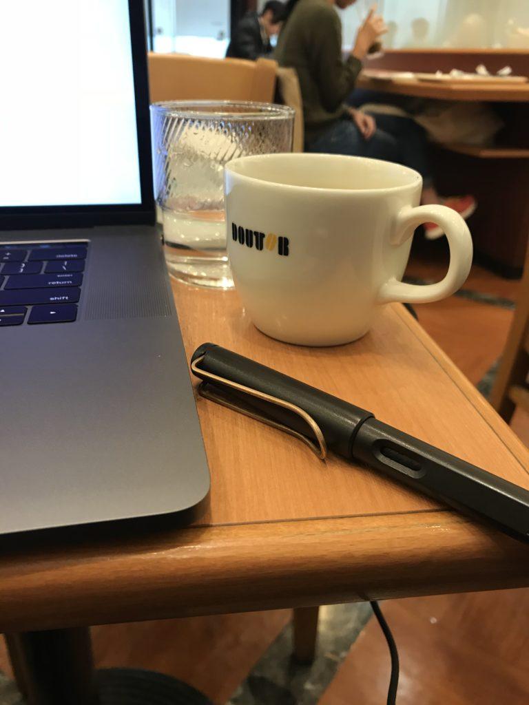 パソコン・ペン・コーヒーカップの写真