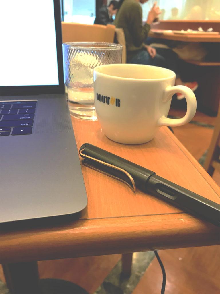 パソコン・ペン・コーヒーカップの写真(編集途中)